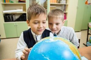 школьники изучают глобус на уроке
